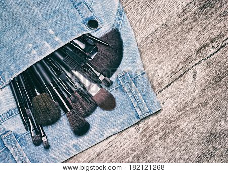 Professional tools of makeup artist in blue jeans pocket on shabby wooden surface. Make up brushes and applicators. Toned image with copy space
