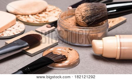 Essential products for face makeup: liquid foundation, concealer, powder. Shallow depth of field