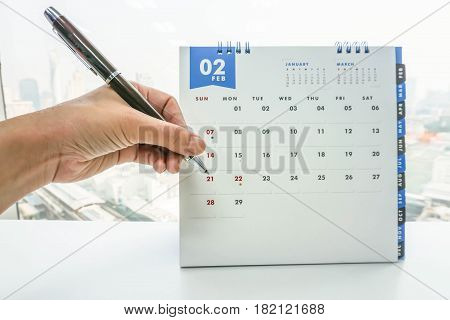 businesswoman hand with pen note business meeting on February calendar