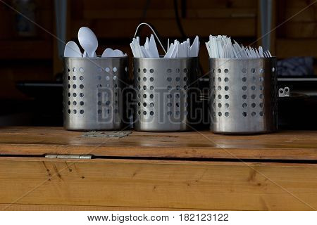plastic cutlery in stainless steel containers at the sales counter at food stall