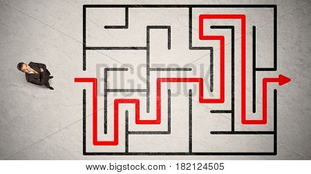 Lost businessman found the way in maze with red arrow on grungy background