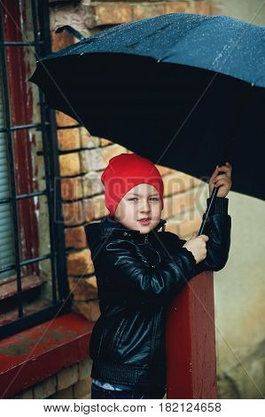 the boy holding the umbrella the Spring walking in the rain