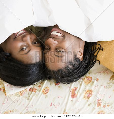 African couple laying under sheet in bed