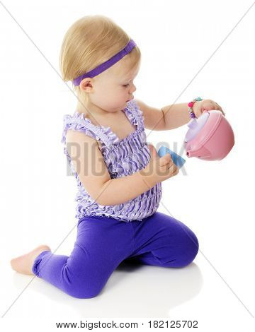 Side view of an adorable 2-year-old pouring imaginary tea from her pastel tea set.  On a white background.