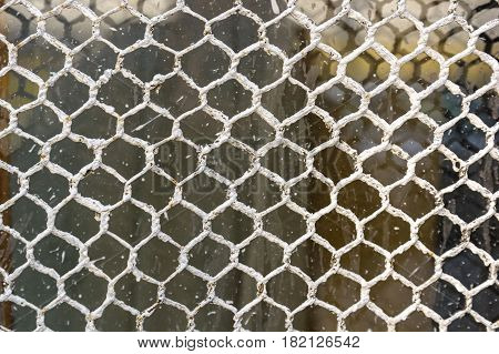 Closeup obsolete metal netting with white paint abstract background texture