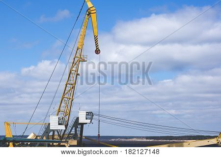 Port Crane With Yellow Arrow Against The Blue Sky And Clouds. River Port Equipment For Unloading Shi
