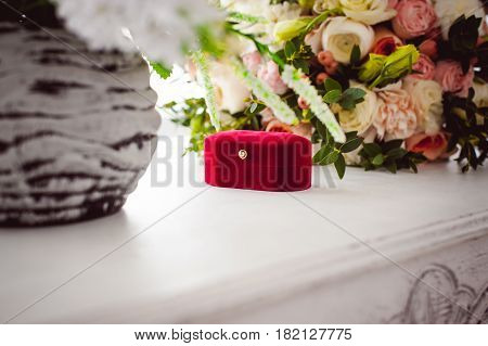 Photo Image Of A Red Velvet Box With Wedding Rings Of The Bride And Groom, On A White Table, With A