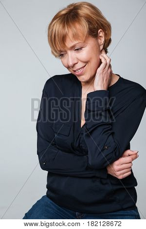 Image of a cheerful mature woman sitting and posing isolated over grey wall. Looking aside.