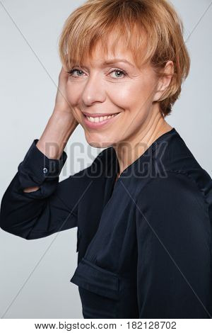 Vertical image of a happy elderly woman standing sideways and looking at the camera over gray background