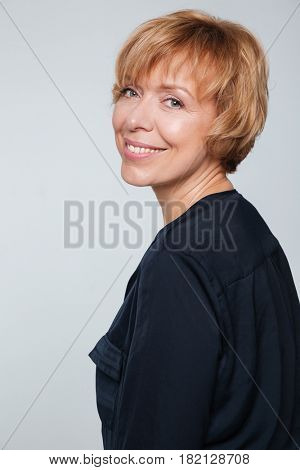 Vertical image of smiling elderly woman standing sideways and looking at the camera over gray background