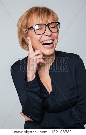 Portrait of a laughing mature woman wearing glasses sitting and posing isolated over grey wall. Eyes closed.