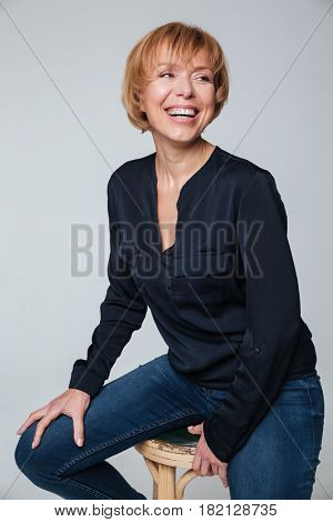 Portrait of a happy mature woman sitting and posing isolated over grey wall. Looking aside.