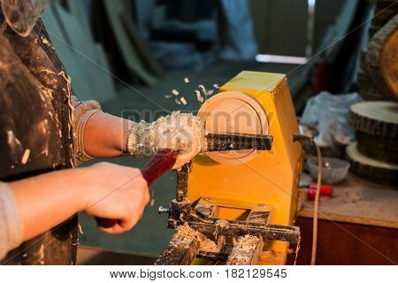 woman turning a wooden plate on a lathe in a carpenter's workshop