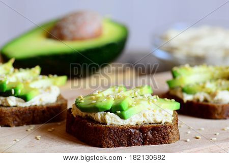 Hearty chickpeas hummus and avocado sandwiches on a wooden board, avocado half, hummus in a glass bowl. Veggie sandwiches cooked with rye bread, avocado slices, chickpeas hummus and fried sesame seeds