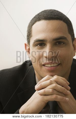 Hispanic businessman with hands clasped