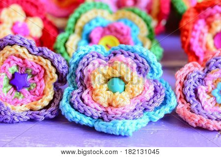 Bright crochet flowers on purple wooden background. Flowers crocheted from colorful cotton yarn. Simple summer handmade DIY idea. Closeup