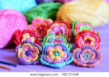Colorful crochet flowers collection. Crochet flowers, multicolored cotton yarn, crochet hooks on purple wooden table. Easy summer handmade crafts idea. Closeup