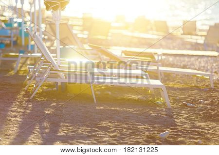 Loungers on beach deserted seaside at amazing sunrise.