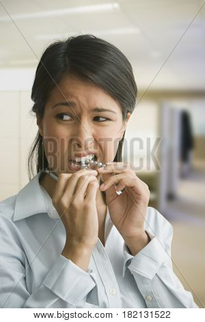 Eurasian woman biting necklace