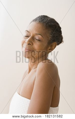 Mixed race woman wrapped in towel smiling