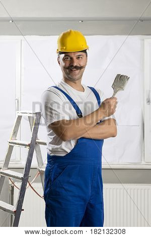 Manual worker wearing bib overalls holding paintbrush.
