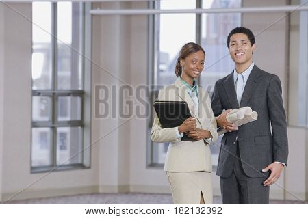 Multi-ethnic business people holding blueprints and binder