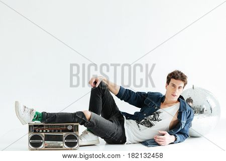Image of concentrated young man sitting isolated over white background with disco ball and boombox. Looking at camera.