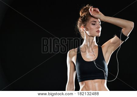 Tired fitness woman touching her forehead and listening to music in studio over black background