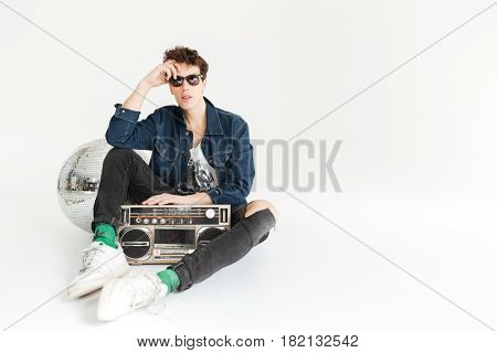 Picture of serious young man wearing sunglasses sitting isolated over white background with disco ball and boombox. Looking at camera.