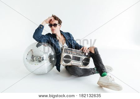 Image of handsome young man wearing sunglasses sitting isolated over white background with disco ball and boombox. Looking aside.