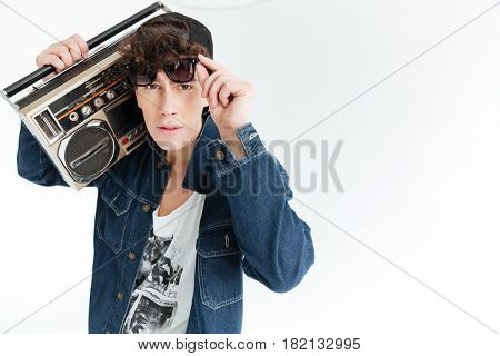 Image of handsome young man wearing sunglasses standing isolated over white background and holding boombox. Looking at camera.