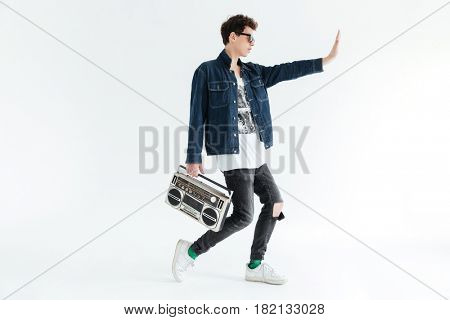 Picture of handsome young man wearing glasses posing isolated over white background and holding boombox. Looking aside.