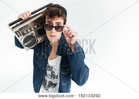 Picture of handsome young man wearing glasses standing isolated over white background and holding boombox. Looking at camera.