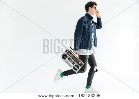 Image of attractive young man wearing glasses posing isolated over white background and holding boombox. Looking aside.
