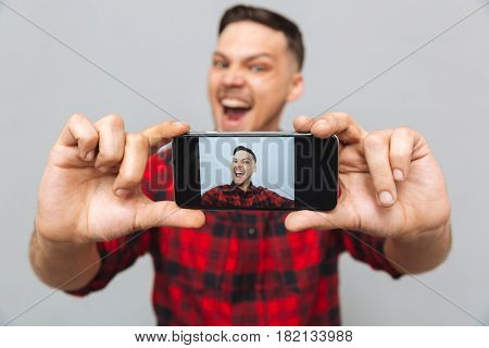 Close up image of a  happy man in shirt  making photo on his  smartphone over gray background