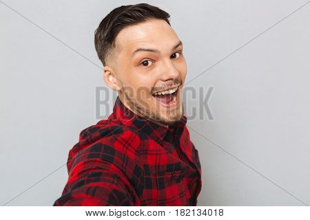 Happy man in shirt standing sideways and looking at camera over gray background. Close up portrait