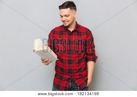 Smiling man in red shirt reading book in studio and holding arm in pocket over gray background