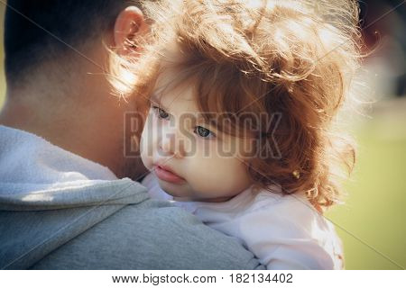 Child on father's shoulder in park