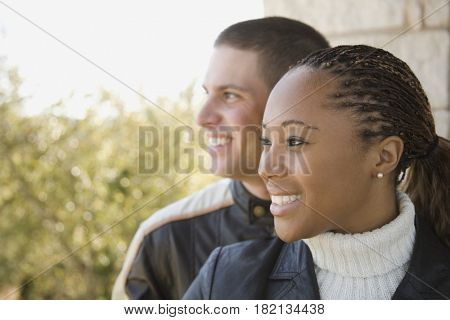Multi-ethnic couple looking at view on balcony