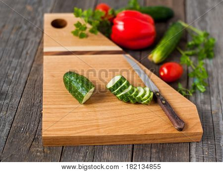 exquisite oak cutting board with vegetables on rustic wooden background