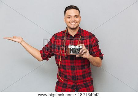 Smiling man in shirt holding copyspace on the pound and holding retro camera in second hand over gray background