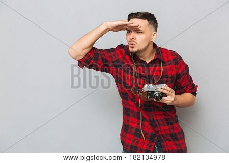 Young man in shirt holding retro camera and looking away