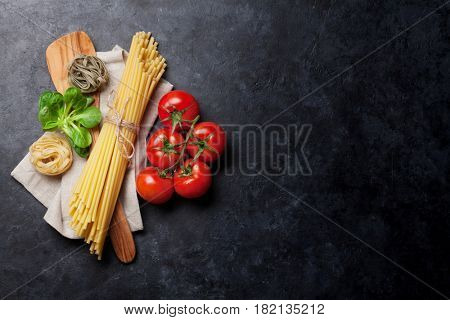 Pasta and ingredients on stone table. Top view with copy space