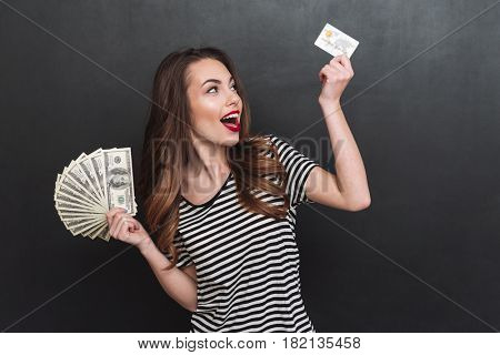 Picture of smiling young lady standing over grey wall and holding money and debit card in hands. Looking aside.