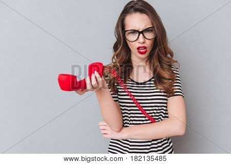 Image of confused young lady standing over grey wall holding phone. Looking at camera.