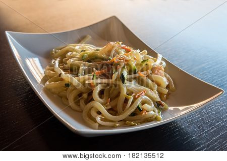 delicious japanese food yaki udon noodles with seafoodshrips and vegetableswhite plate on wooden backgroung.