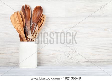 Kitchen utensils in front of wooden wall with space for your text