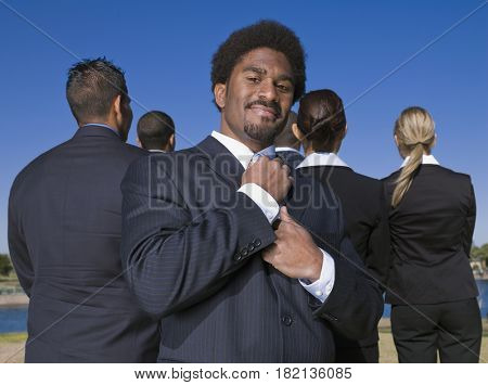 African businessman adjusting tie behind co-workers