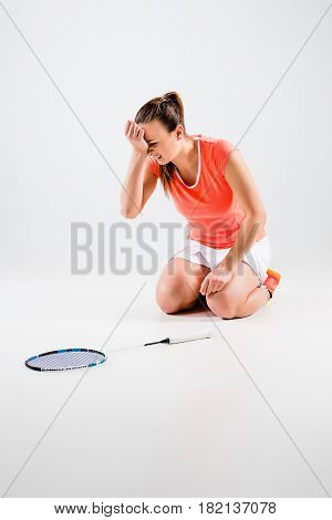 Young woman playing badminton over white studio background. A symbol of defeat and failure
