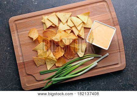 Bowl with beer cheese dip and nacho on wooden board